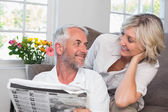 Couple looking at each other while reading newspaper — Stock Photo