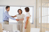 Business people shaking hands besides colleague at office — Stock Photo