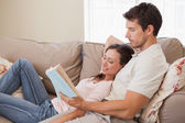 Relaxed young couple reading book on couch — Stock Photo