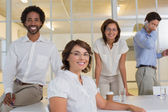 Smiling businesswoman with colleagues at office — Stock Photo