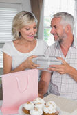 Mature man giving a gift box to happy woman — Stock Photo