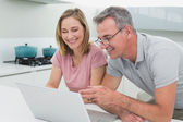 Happy couple using laptop in kitchen — Stock Photo