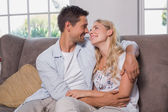 Relaxed loving couple sitting on sofa — Stock Photo