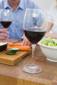Mid section of couple with wine glasses and vegetables — Stock Photo