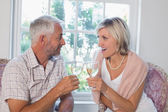 Happy mature couple with wine glasses at home — Stok fotoğraf