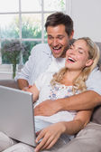Cheerful casual couple using laptop in living room — Stock Photo
