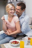 Man embracing woman at breakfast table at home — Stock Photo