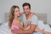 Happy relaxed young couple sitting in bed — Stock Photo