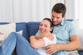 Portrait of a loving couple sitting on couch — Stock Photo