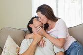 Loving relaxed couple kissing in living room — Stock Photo