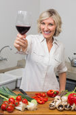 Happy mature woman with vegetables and wine glass in kitchen — Stok fotoğraf