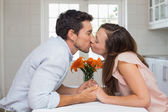 Side view of a loving couple kissing in kitchen — Stock Photo