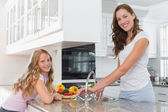 Girl helping her mother to wash vegetables in kitchen — ストック写真