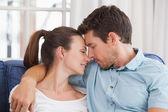 Loving couple jeune avec les yeux fermés sur canapé — Photo