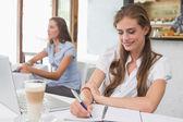 Mulher escrevendo notas com laptop na cafeteria — Fotografia Stock