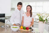 Portrait of happy young couple in the kitchen — Stock Photo