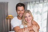 Man embracing woman from behind at home — Stock Photo