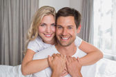 Loving woman embracing man from behind at home — Fotografia Stock