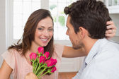 Happy woman and man with flowers at home — Stock Photo