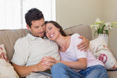 Loving couple sitting on couch at home — Stock Photo