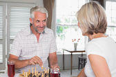 Mature couple with drinks while playing chess — Stock Photo