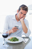 Man text messaging at food table — Stock Photo