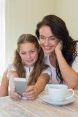 дочь с матерью, принимая автопортрет через мобильный телефон — Стоковое фото