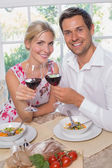 Loving couple with wine glasses sitting at dining table — Stock Photo