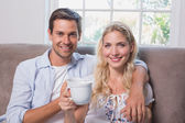Portrait of a loving couple with coffee cups in living room — Stock Photo