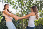 Happy woman and girl holding hands under the tree — Stock Photo