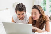 Smiling couple using laptop in bed — Stock Photo
