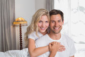 Loving woman embracing man from behind at home — Stock Photo