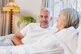 Smiling relaxed mature couple lying in bed — Stock Photo