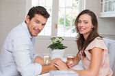 Portrait of smiling couple with wine glasses at home — Stock Photo