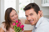 Cheerful woman looking at man with flowers — Stock Photo