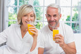 Mature couple holding orange juices at home — Stock Photo