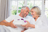 Woman giving mature man a gift box — Stok fotoğraf