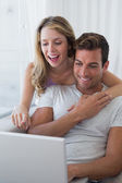 Relaxed couple using laptop on couch — Stock Photo