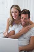 Miłej pary za pomocą laptopa na kanapie — Zdjęcie stockowe