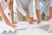 Mid section of business people working on blueprints at office — Stock Photo