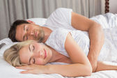 Relaxed couple lying in bed with eyes closed — Stock Photo