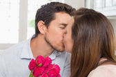 Close-up of a loving couple kissing with flowers — Stock Photo