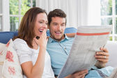 Happy couple reading newspaper on couch — Stock Photo