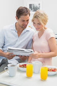 Couple reading newspaper while having breakfast at home — Stock Photo