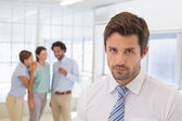 Colleagues gossiping with sad businessman in foreground — Foto Stock