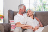 Relaxed mature couple sitting on couch — Stock Photo