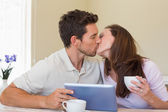 Couple kissing while using digital tablet — Stock Photo
