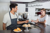Friendly waiter giving coffee to a woman at coffee shop — Stock Photo