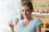 Smiling woman drinking coffee in the coffee shop — Stock Photo