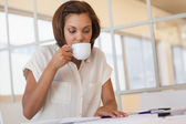 Businesswoman drinking coffee while working on blueprint — Stock Photo